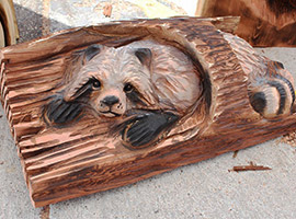Raccoon in Log Chainsaw Carving